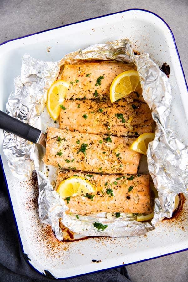 baking dish with lemon garlic butter salmon in foil