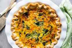 white pie dish with a spinach bacon quiche inside