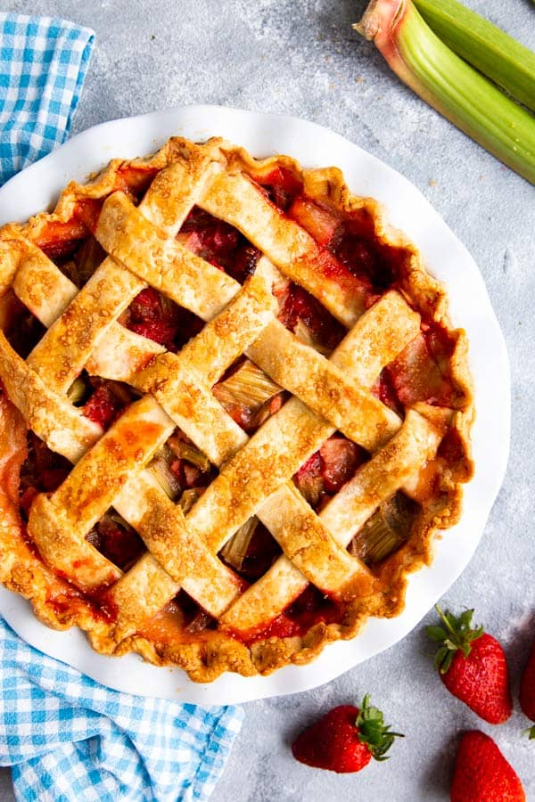 strawberry rhubarb pie with lattice crust in a white pie plate