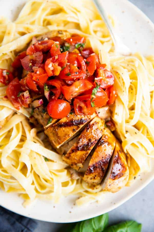 close up photo of grilled balsamic bruschetta chicken on top of fettuccine