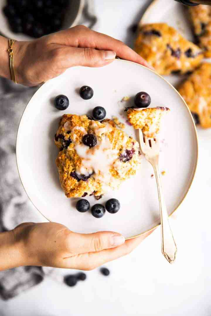 female hands holding plate with blueberry scone