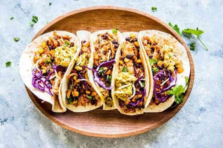 southwestern crockpot chicken tacos on a wooden platter