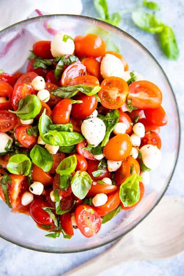 glass bowl with caprese cherry tomato salad