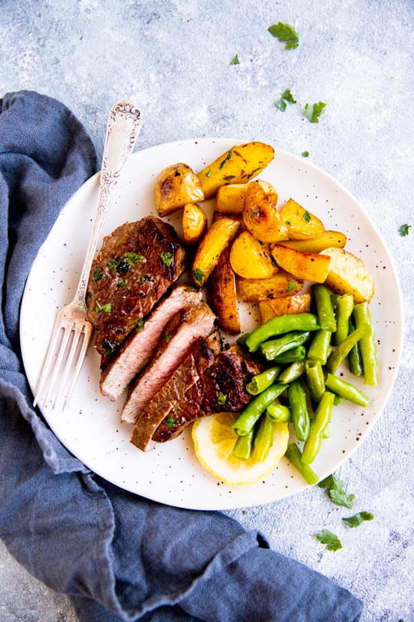 cooked steak on a white plate with potatoes and green beans