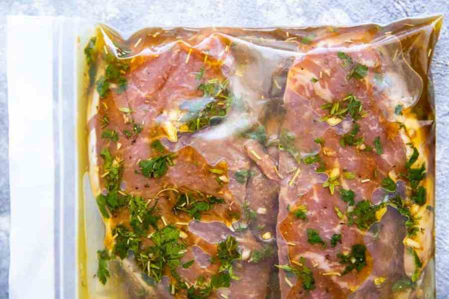 close up photo of a ziploc bag filled with steak in marinade