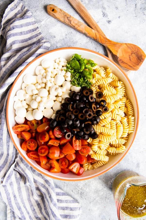 ingredients for pesto pasta salad in a bowl