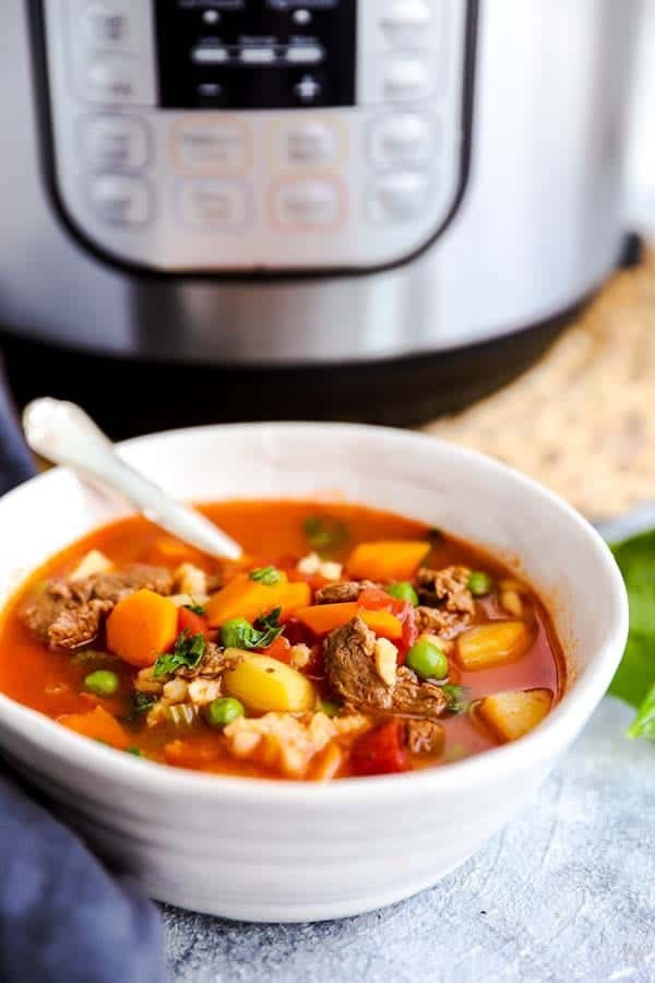 bowl of beef barley soup in front of an electric pressure cooker