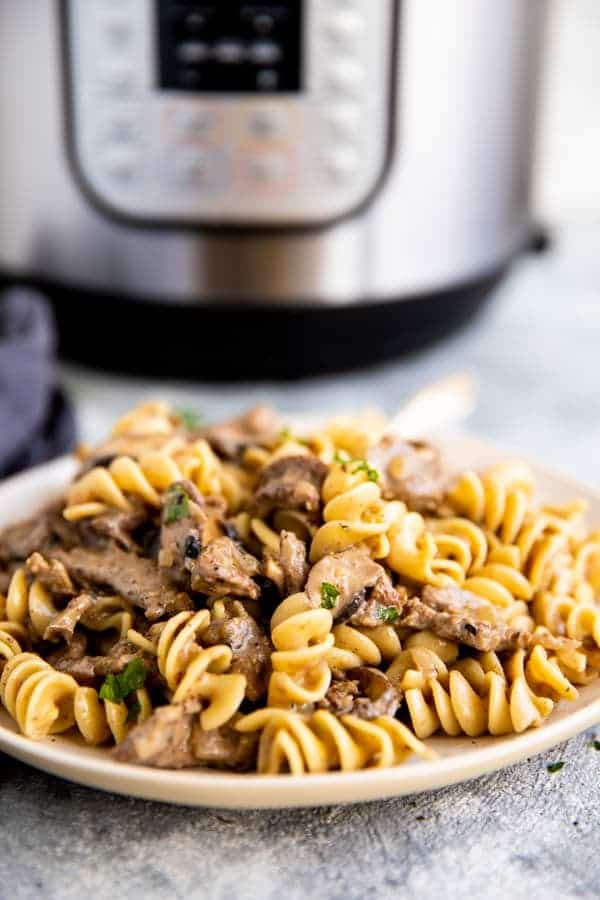 plate with noodles and stroganoff sauce in front of an instant pot electric pressure cooker