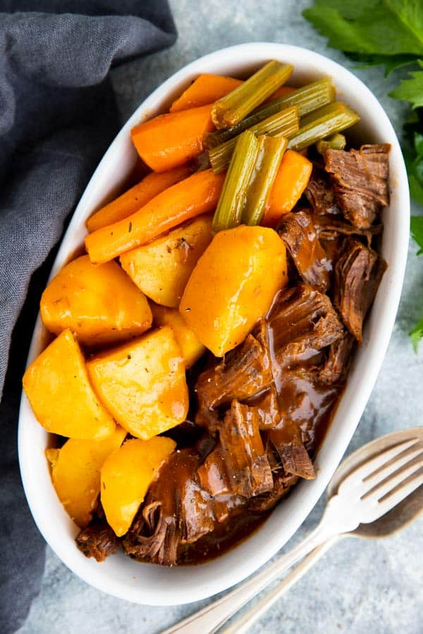 white dish with potatoes, carrots and beef roast in gravy