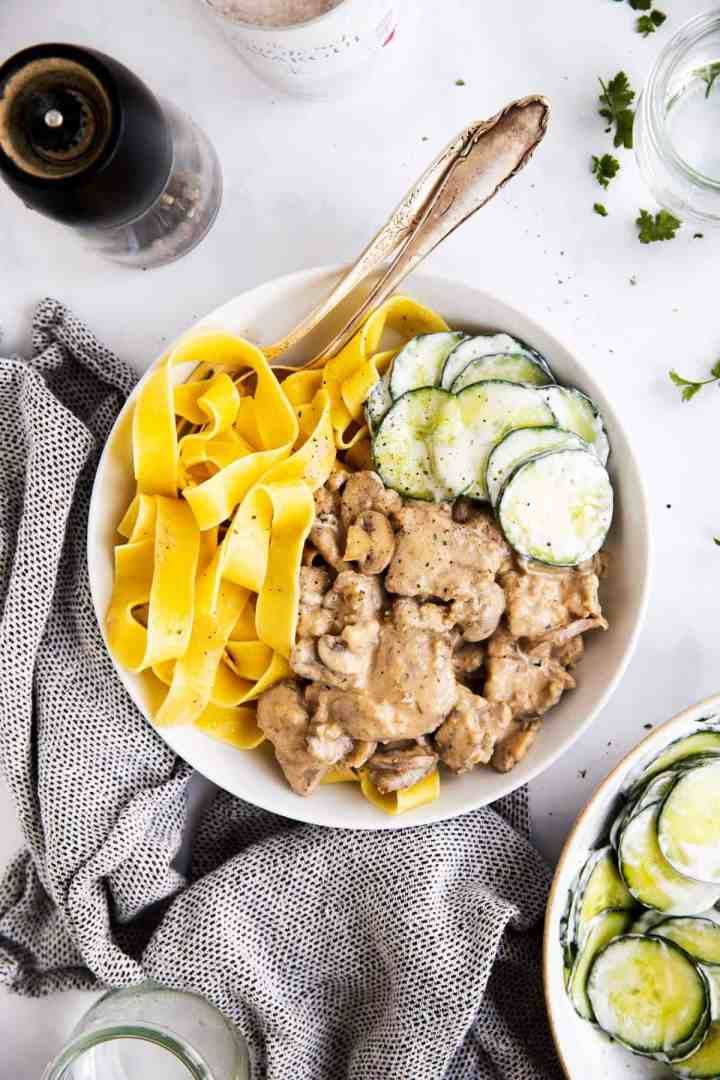 view from overhead on a white plate with stroganoff, egg noodles and cucumber salad