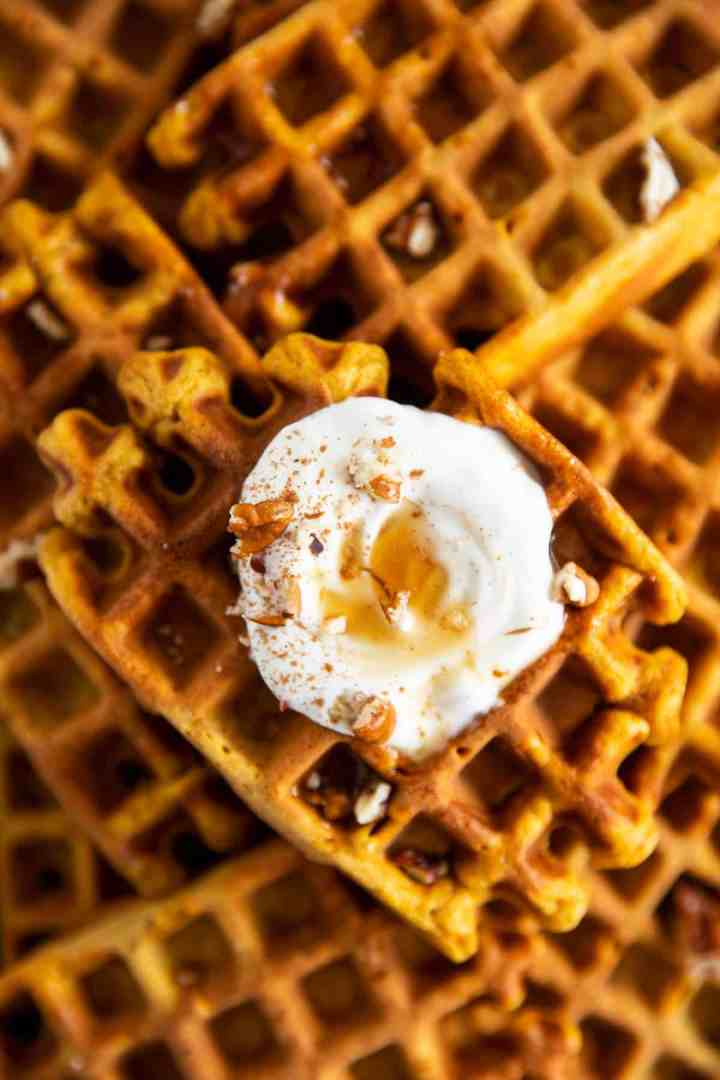 close up of pumpkin waffles with frosting and maple syrup