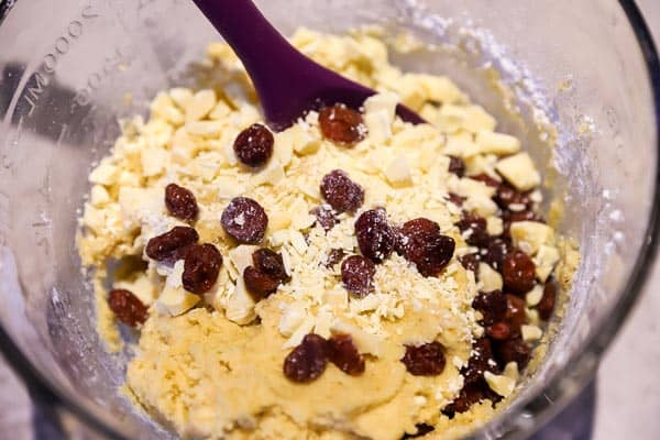 stirring dried cranberries and white chocolate chunks into cookie dough
