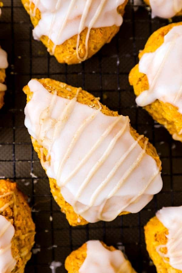 close up photo of a glazed pumpkin scone on a cooling rack