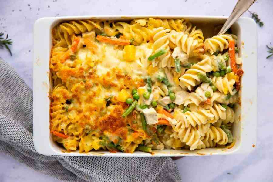 White casserole dish filled with turkey noodle bake On a marble countertop