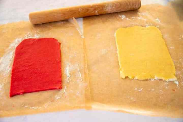 red and plain sugar cookie dough rolled out on wax paper