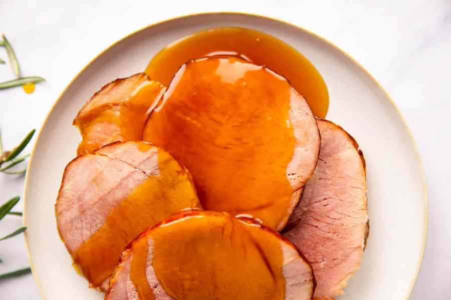 white plate with slices of ham covered in honey glaze