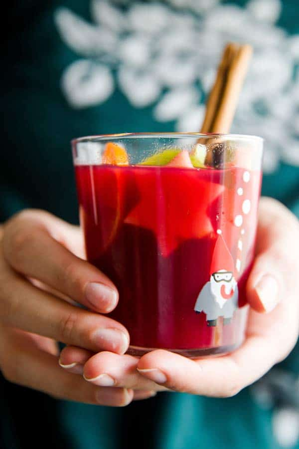 woman in green sweater holding a glass of Christmas punch