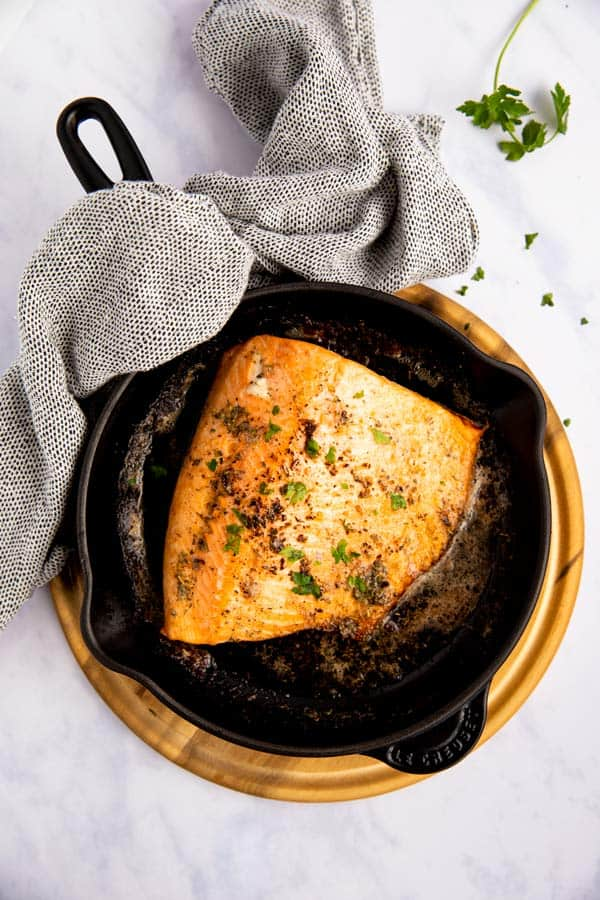 piece of salmon fillet baked in a cast iron skillet
