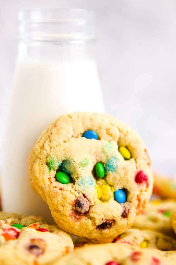 m&m cookie leaning against a bottle of milk