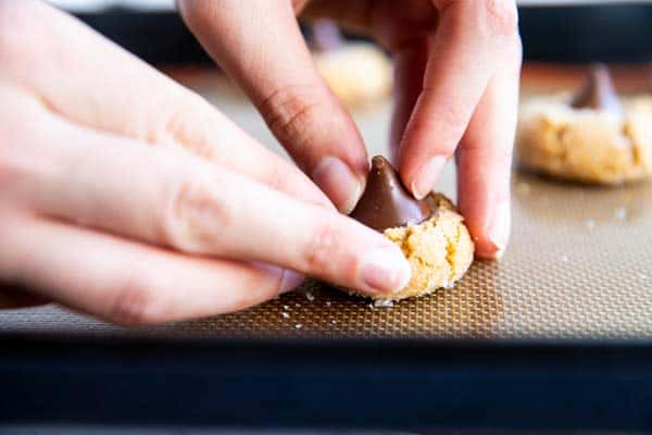 female hands pushing a chocolate kiss into a baked peanut butter cookie