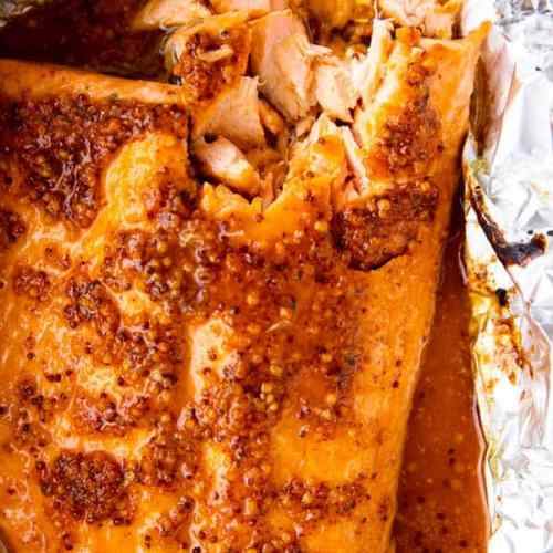 top down view of baked salmon side with maple dijon glaze on a piece of aluminum foil