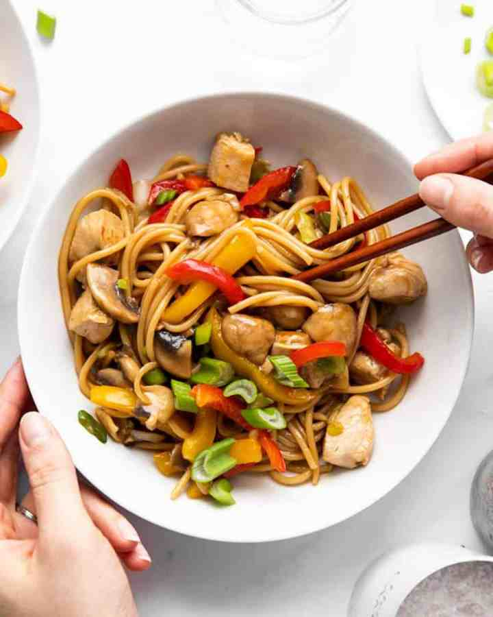 female hands holding a plate with chicken lo mein