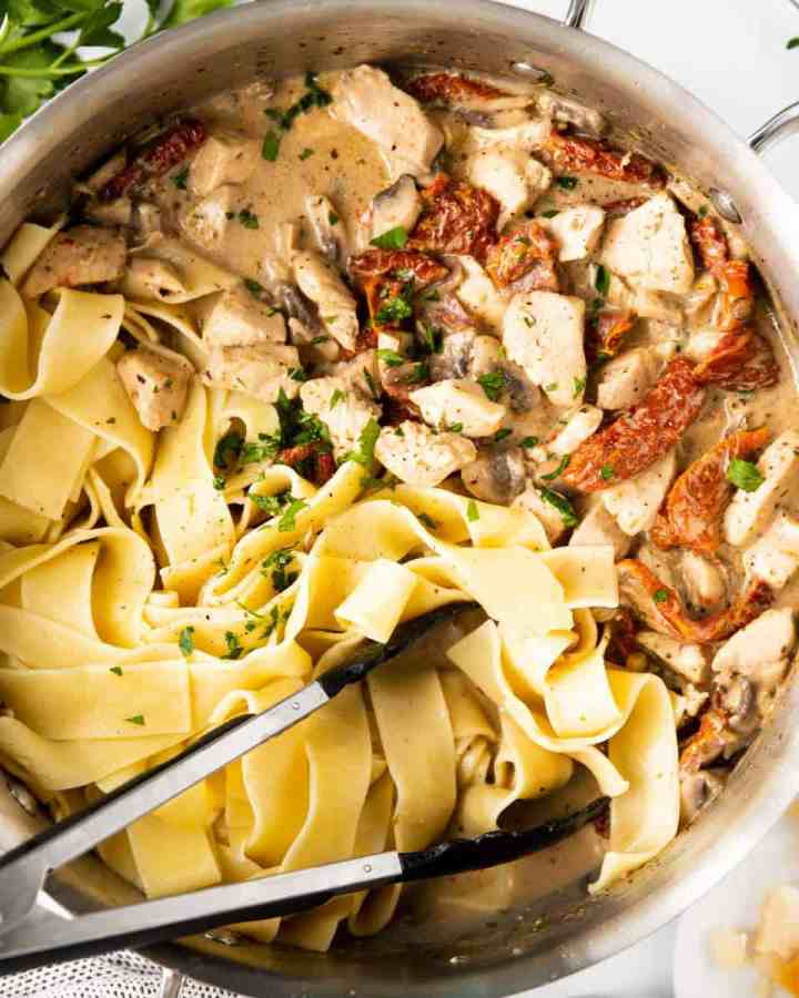 top down view on pan filled with chicken pasta and creamy sun-dried tomato sauce