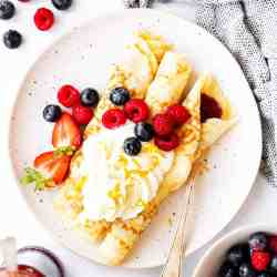 top down view on plate with crepes, whipped cream and berries