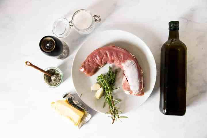 ingredients to make pork tenderloin on white marble surfacer
