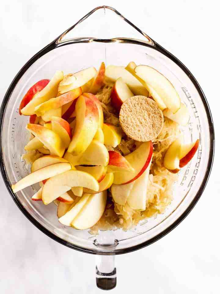 glass bowl with apples, sauerkraut, maple syrup and brown sugar