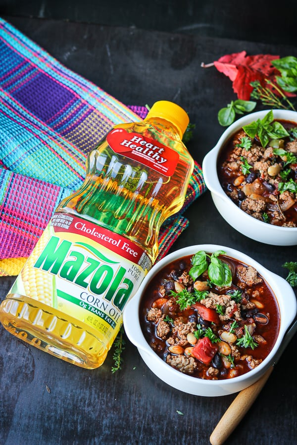 Two bean turkey chili in white bowls with Mazola oil bottle on the left side.