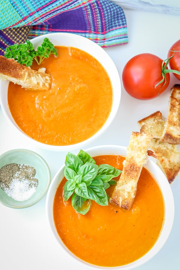 Tomato carrot soup with cheesy bread and fresh basil to garnish