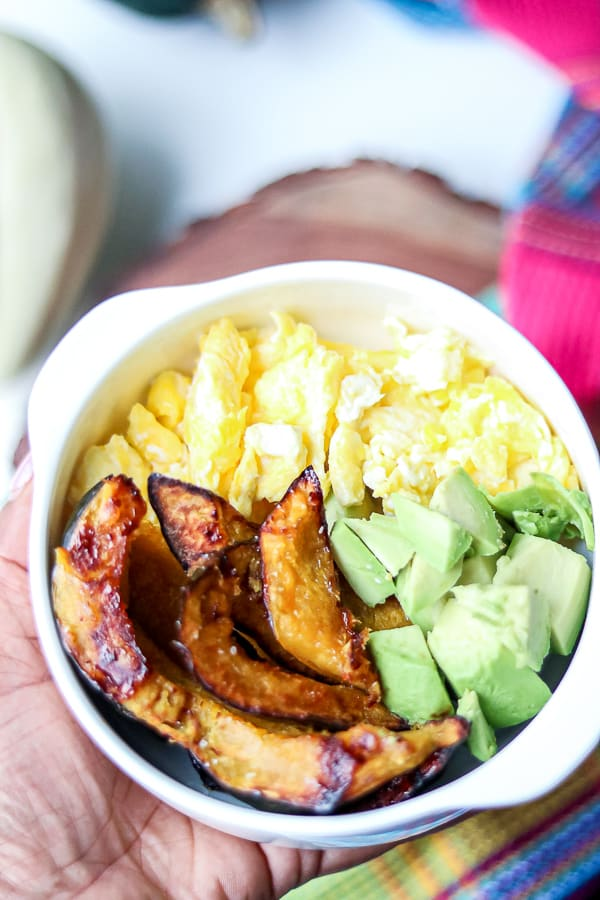 roasted squash with eggs and avocados in a white bowl.