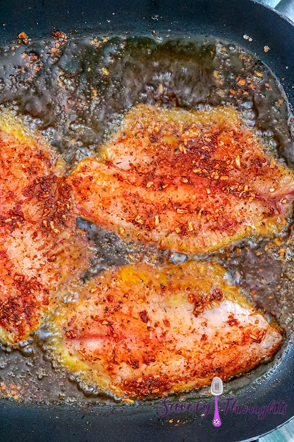 Tilapia fish frying in oil