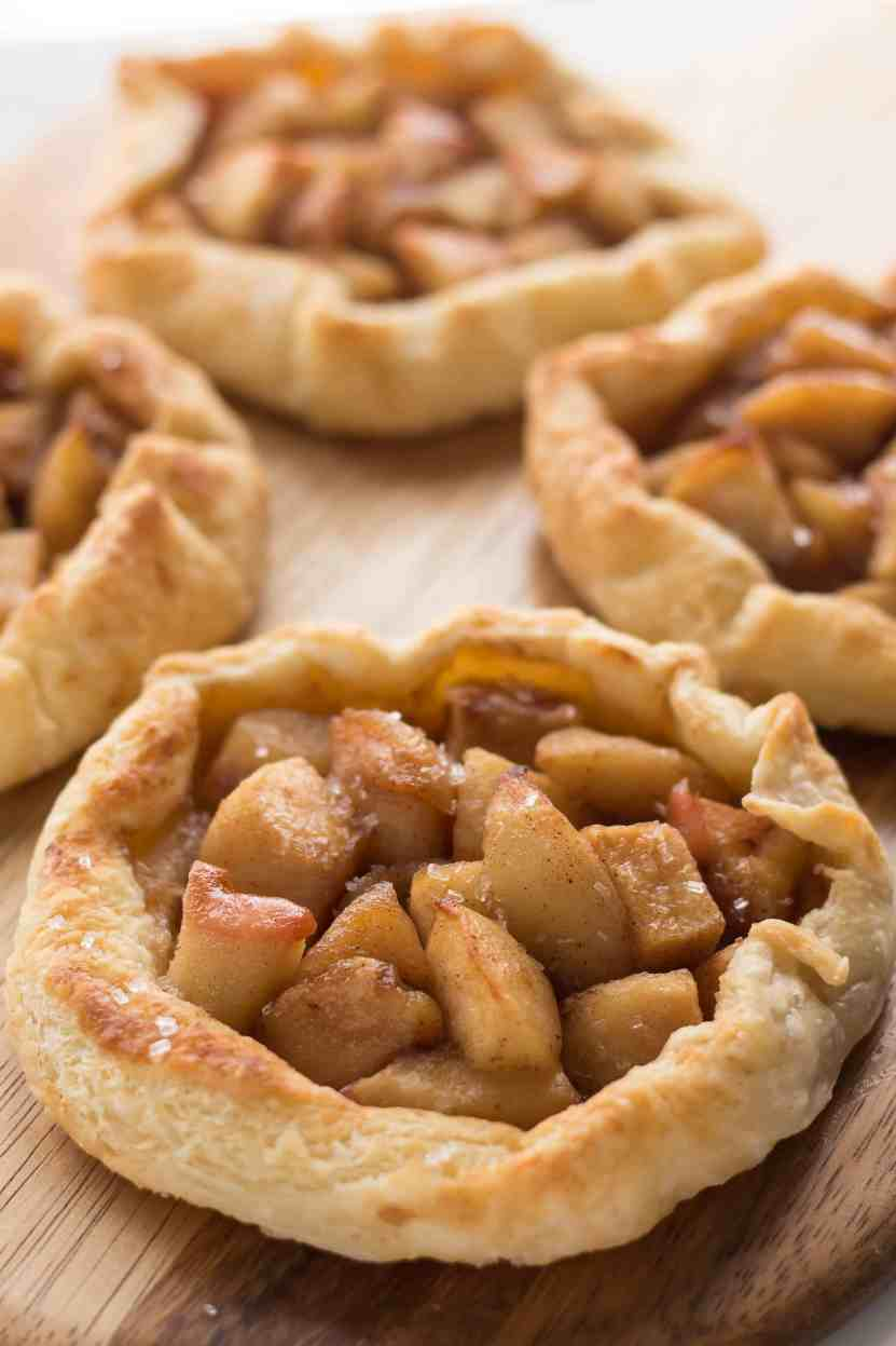 4 homemade individual apple pies on board.