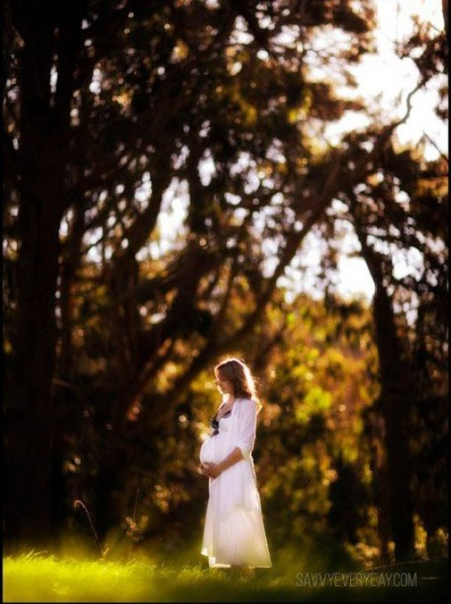 maternity photo of mom at the park in a white gown