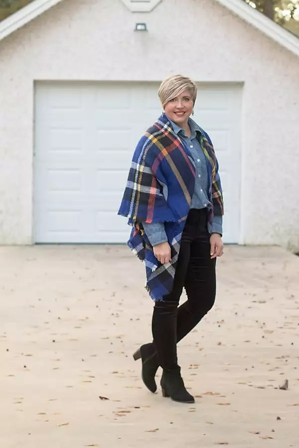 Fashion blogger wearing a plaid blanket scarf as a poncho with a chambray shirt and velvet jeans.