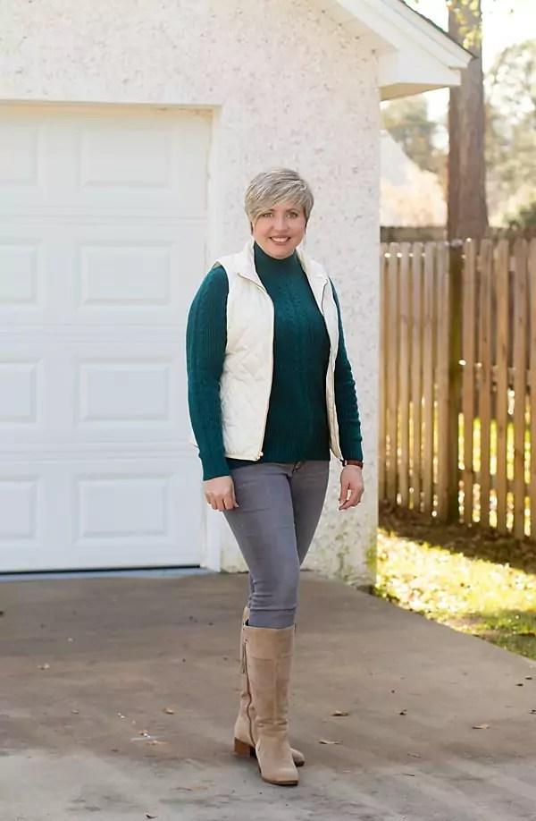 Fashion blogger in green Loft sweater, quilted vest, grey jeans and boots.
