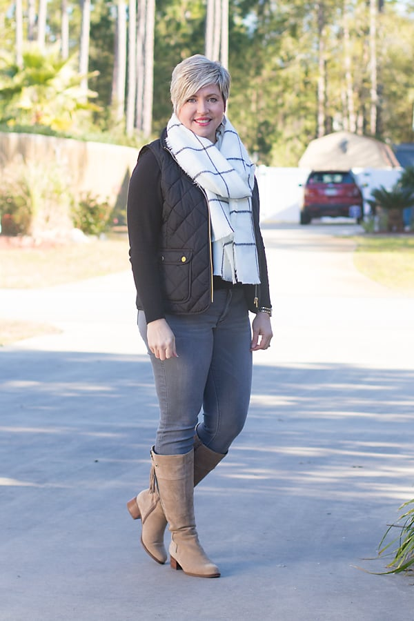 Over 40 fashion blogger in winter outfit with tall boots, vest and scarf.