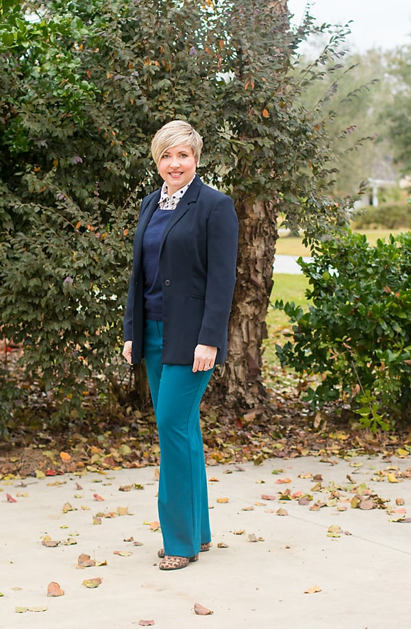 Woman in business attire featuring navy blazer and teal pants