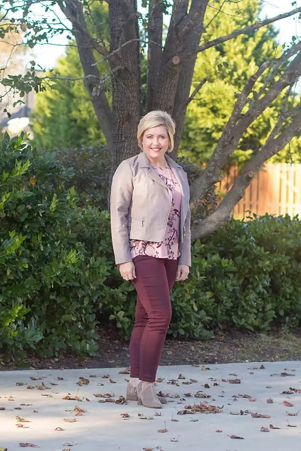 Fall moto jacket outfit with floral top and burgundy jeans
