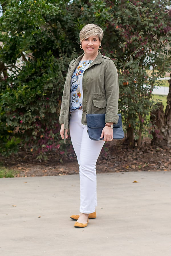 spring outfit with print top and white jeans