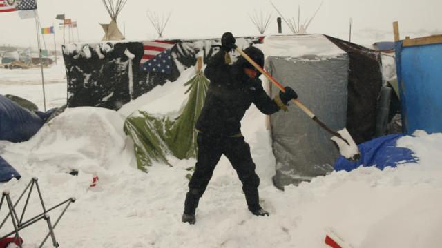 "A camper maintains his shelter as high winds and a blizzard hit the Oceti Sakowin camp while ""water protectors"" continue to demonstrate against plans to pass the Dakota Access pipeline adjacent to the Standing Rock Indian Reservation, near Cannon Ball, North Dakota, U.S., December 6, 2016.  REUTERS/Lucas Jackson"