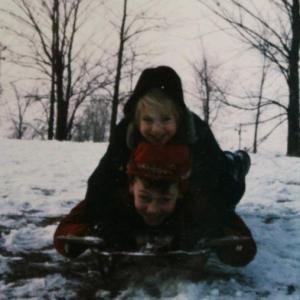 Kim, age 4 or 5, sledding with her brother.