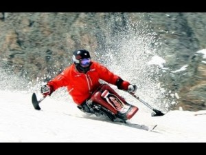 a disabled man in a red jacket skiing skillfully with his sit-ski
