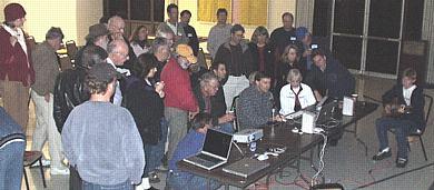 SBMUGers crowd around to watch Harold Adams demonstrate GarageBand with the help of Robert Adams (at right, with guitar).  (Photo: Robert Winokur)