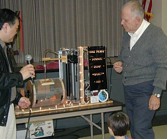Ed Togami (left) and Bruce Gordon look at the ticket-picking machine (Photo: Brian Carlin)