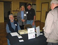 Dick, Cathy & Dale welcome a visitor at the hospitality table