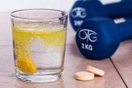 glass of fitness supplement and a dumbbell