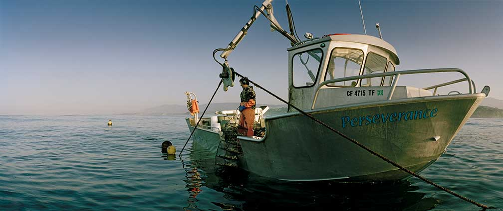 "Bernard working on the boat named the ""Perserverance"" offshore at the Santa Barbara Mariculture farm"